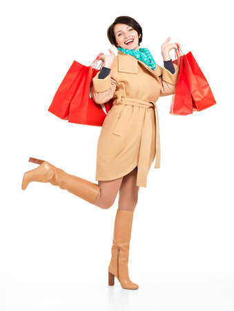 women in boots: Full portrait of happy woman with shopping bags in autumn coat with green scarf standing isolated on white background Stock Photo