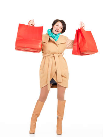 girl boots: Full portrait of happy woman with shopping bags in autumn coat with green scarf standing isolated on white background Stock Photo
