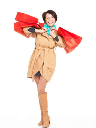 Full portrait of happy woman with shopping bags in autumn coat with green scarf standing isolated on white background Stock Photo - 18352505