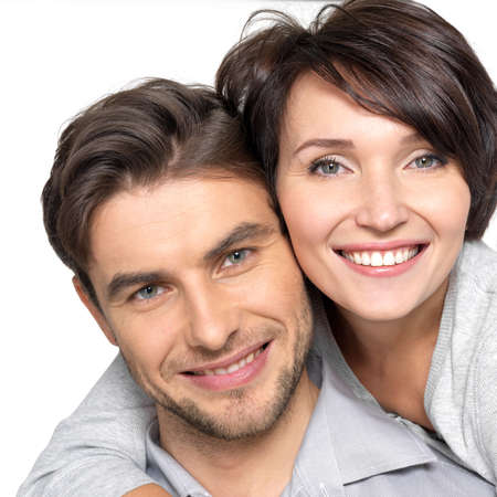 Close-up portret van mooie gelukkige paar geïsoleerd op witte achtergrond. Aantrekkelijke man en vrouw wordt speels.