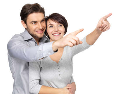 happy couple white background: Portrait of the happy couple looking and pointing into the distance, isolated on white background.  Stock Photo