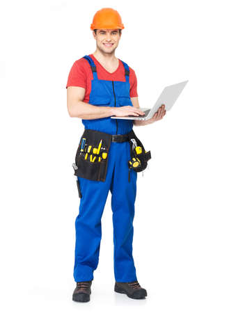 Young worker with  tools holds the laptop full portrait over white background photo