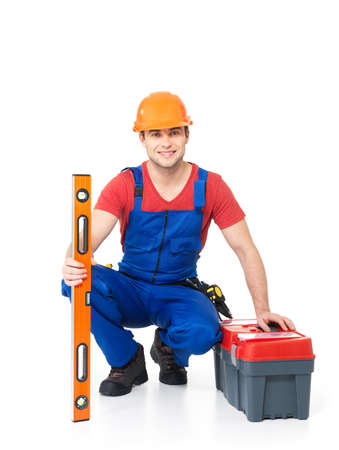 protective workwear: Portrait of smiling manual worker with tools isolated on  white background