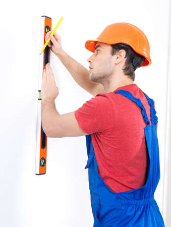 Construction worker with  level on the  wall over white background -  manual worker images. photo