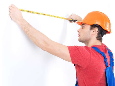 Construction worker measuring the wall over white background -  manual worker images. photo