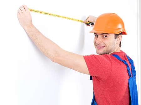 artesano: Trabajador de la construcci�n medici�n de la pared sobre fondo blanco - manual de im�genes de los trabajadores.