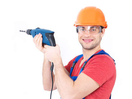 Portrait of a smiling man drilling a hole in the wall. photo