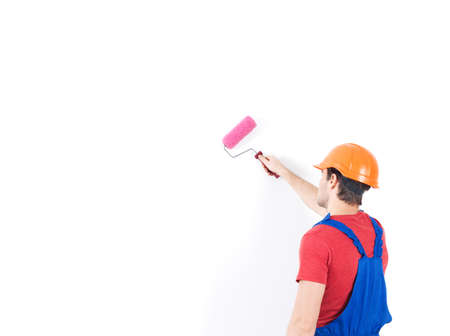 Craftsman painter stands on the stairs with roller, full portrait over white background , rear view photo