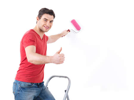 Smiling  worker  painter with brush  showing thumbs up sign isolated on  white background photo