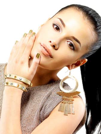 Pretty woman with golden nails and beautiful gold jewelry isolated on white background photo