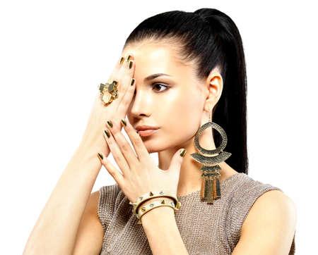 Mujer bonita con clavos de oro y joyas de oro hermosa aislado sobre fondo blanco Foto de archivo