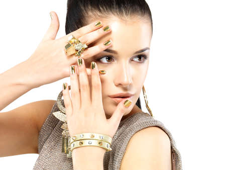 Pretty woman with golden nails and beautiful gold jewelry isolated on white background Stock Photo - 18629139