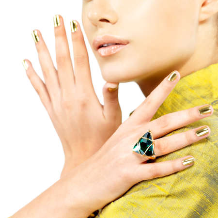 Women hands with golden nails and green precious stone emerald - isolated on white background photo