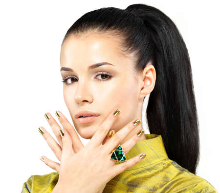 Pretty woman with golden nails and beautiful precious stone emerald - isolated on white background photo