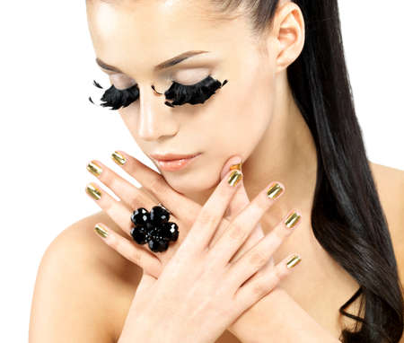 unecht: Closeup Portrait der sch�nen Frau mit langen schwarzen falschen Wimpern Make-up und goldenen N�geln. isoliert auf wei�em Hintergrund