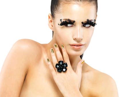 unecht: Gro�ansicht Portr�t der sch�nen Frau mit langen schwarzen falschen Wimpern Make-up und goldenen N�geln. isoliert auf wei�em Hintergrund