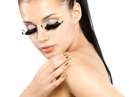 minx: Closeup portrait of the beautiful woman with long black false eyelashes makeup and golden nails.  isolated on white background