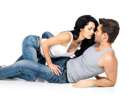Beautiful sexy couple in love on white background dressed in blue jeanse and white undershirt photo