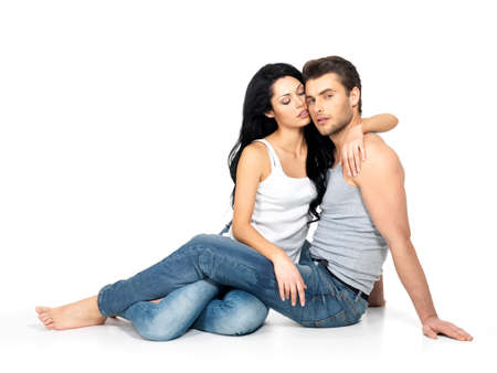 Beautiful sexy couple in love on white background dressed in blue jeanse and white undershirt Stock Photo - 18629074