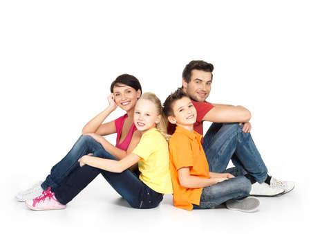 familia abrazo: Retrato de la familia feliz con dos ni�os que se sientan en el estudio sobre el suelo blanco Foto de archivo