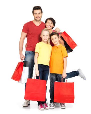 chicas comprando: Familia feliz con bolsas de la compra de pie en el estudio sobre fondo blanco