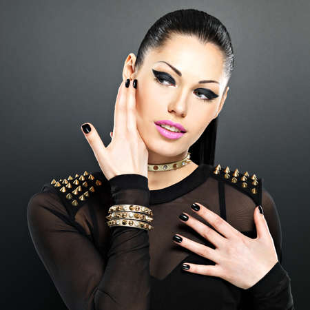 Beautiful face of fashion woman with black nails and bright makeup.  Sexy stylish girl with bracelet thorns on the neck Stock Photo - 18629164