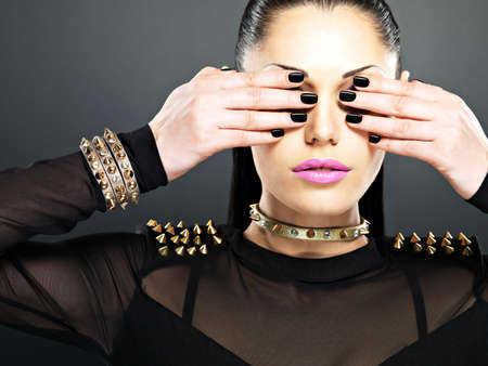 Fashion woman with black nails and bright pink lips.  Stylish girl with bracelet thorns on the neck photo