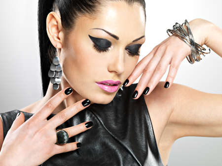 Beautiful fashion woman with black nails at pretty face. Pretty girl model with stylish bijouterie of silver color. 免版税图像