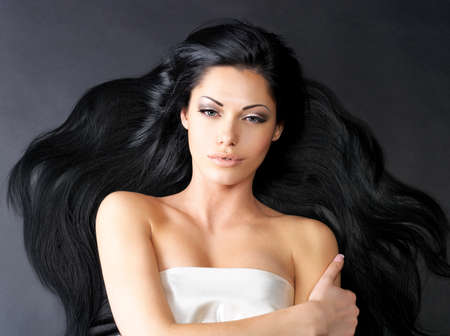 Portrait of a beautiful woman with long straight black hair lying on the dark background photo