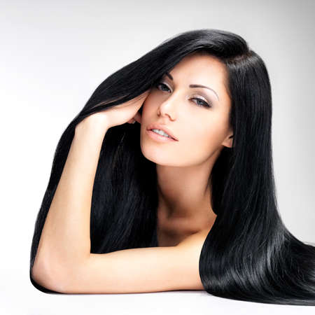 Portrait of a beautiful brunette woman with long straight hair poses at grey background photo