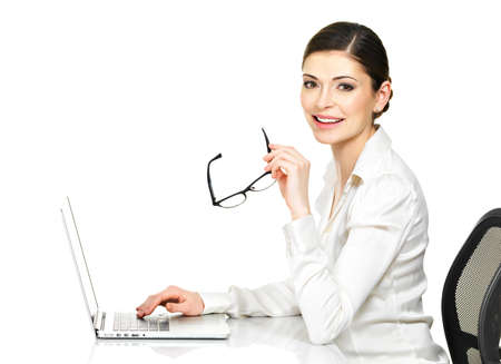 Beautiful smiling woman sits from the  table and working on laptop in white shirt - isolated on white. 
