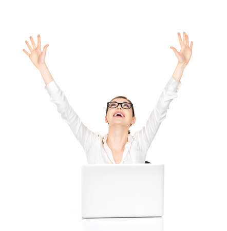 Successful business woman with laptop raised hands up - isolated on white.   photo