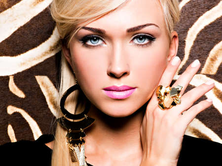Closeup portrait of beautiful face of sexy woman with fashion makeup and gold ring on finger Stock Photo - 18856281