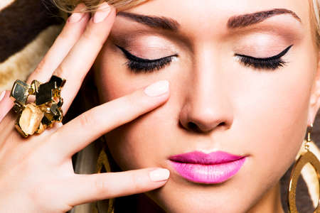 Closeup portrait of beautiful face of sexy woman with fashion makeup and gold ring on finger photo