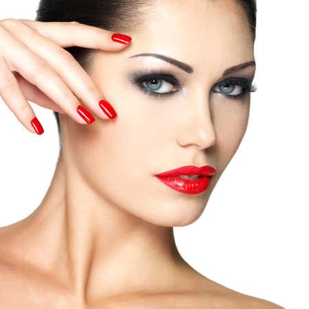 manicura: Joven y bella mujer con las u�as de color rojo y maquillaje de moda - aislado en fondo blanco