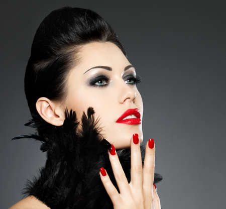 eye makeup: Beautiful fashion woman with red nails, creative hairstyle and makeup - Model posing in studio