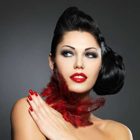 nail design: Beautiful fashion woman with red nails, creative hairstyle and makeup - Model posing in studio