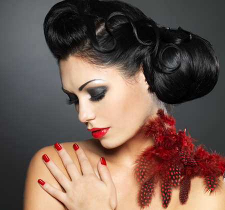 black boa: Fashion young woman with red nails, creative hairstyle and makeup - Model posing in studio