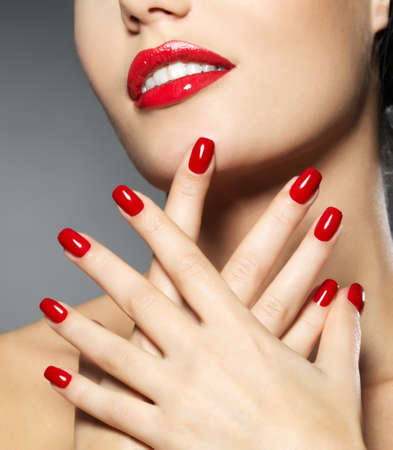 red nail colour: Young woman with fashion red nails and sensual lips - Model posing in studio