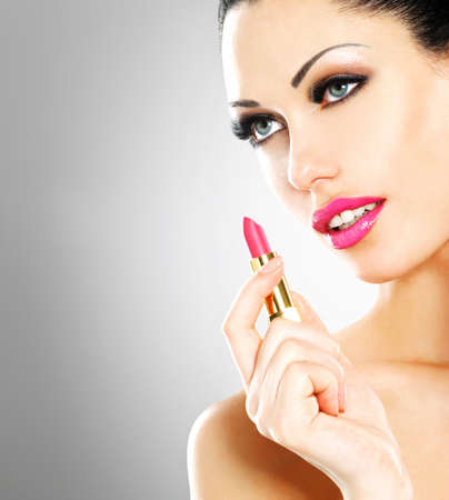 Beautiful woman makes makeup applying pink lipstick on lips.  photo