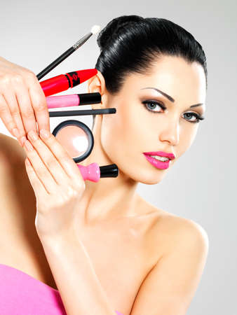 Beautiful woman with makeup cosmetic tools near her face.  Stock Photo - 18856286