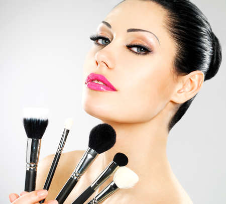 Beautiful woman with makeup brushes near her face. Pretty girl poses at studio with cosmetic tools Stock Photo - 18856270
