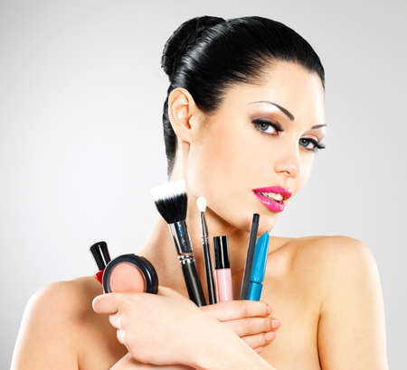 Beautiful woman with makeup brushes near her face. Pretty girl poses at studio with cosmetic tools Stock Photo - 18856269