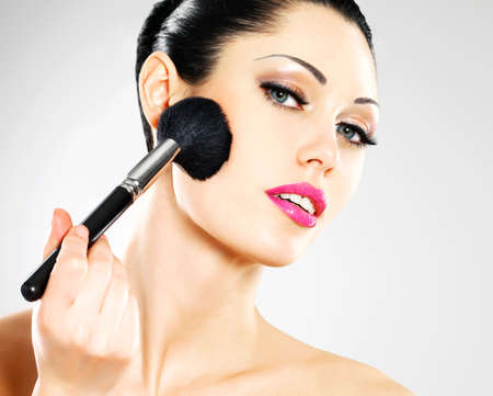 Portrait of  beautiful woman applying blusher on face using cosmetic brush Stock Photo - 18856259