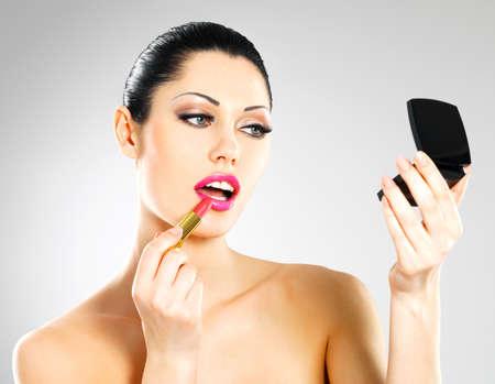Beautiful woman makes makeup applying pink lipstick on lips. Stock Photo - 18856267