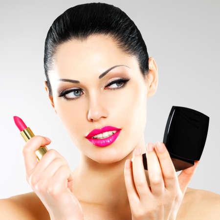 lapiz labial: Mujer hermosa hace maquillaje aplica el l�piz labial de color rosa en los labios.