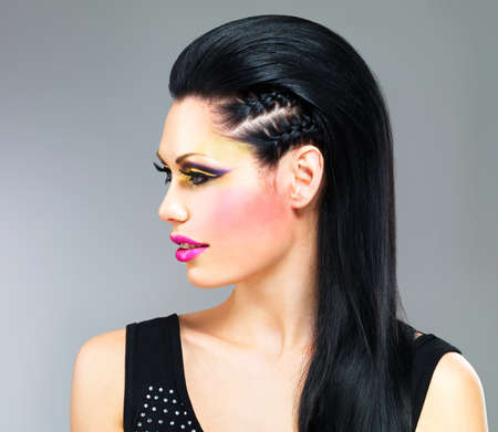 Profile portrait of a woman with fashion makeup on  face and black straight hair photo