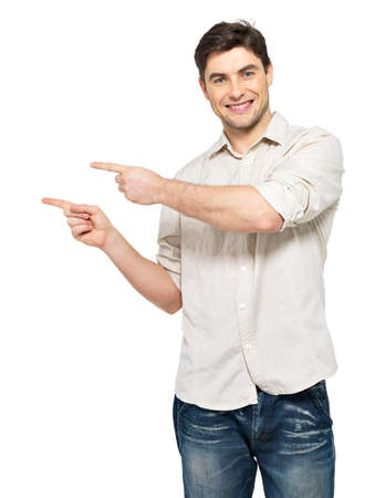 side light: Young smiling man points with fingers in the right side isolated on white background.