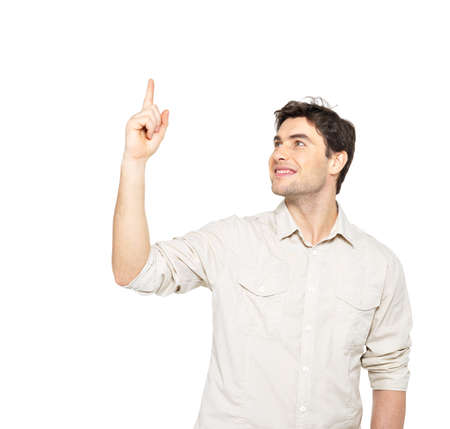 casuals: Young smiling man points with finger on something in  casuals isolated on white background.