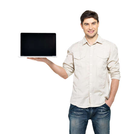 casual man: Portrait of smiling happy man holds laptop on palm with blank screen - isolated on white. Concept communication.